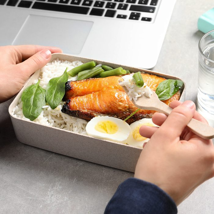 Woman eating natural protein food from container at office table