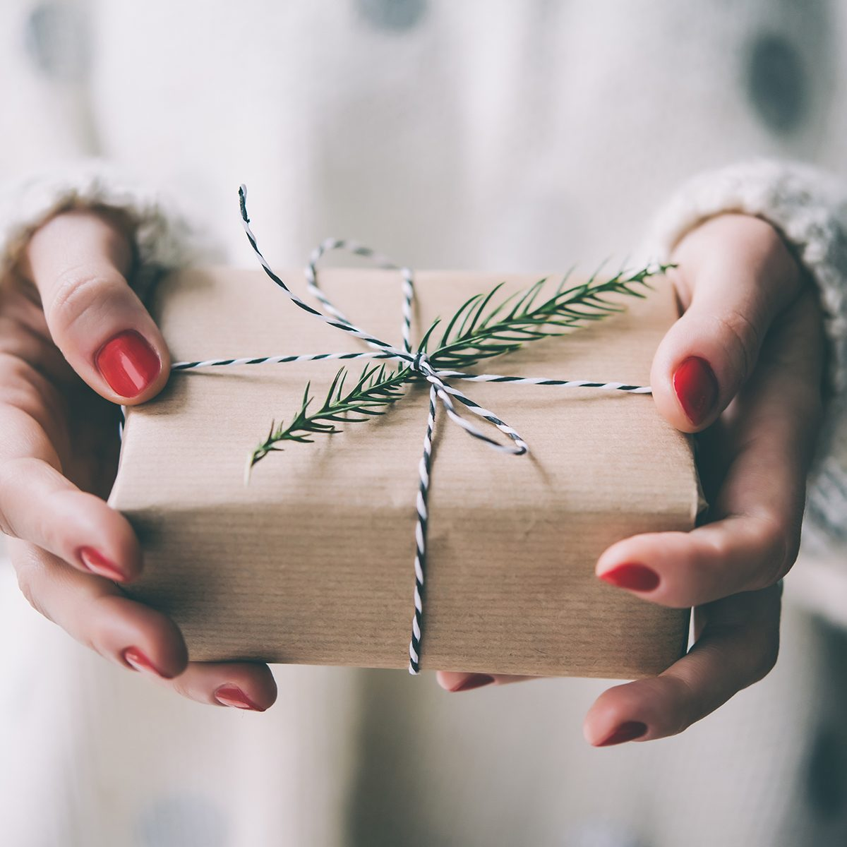 Woman's hands hold christmas or new year decorated gift box.