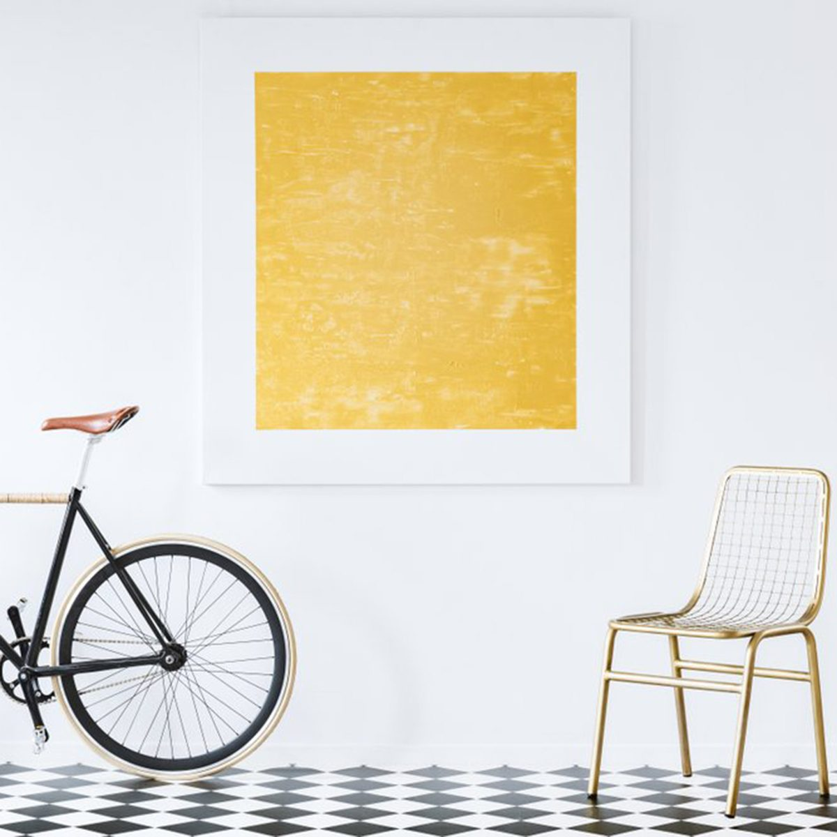Fine art hanging on the wall with a bike and chair below it