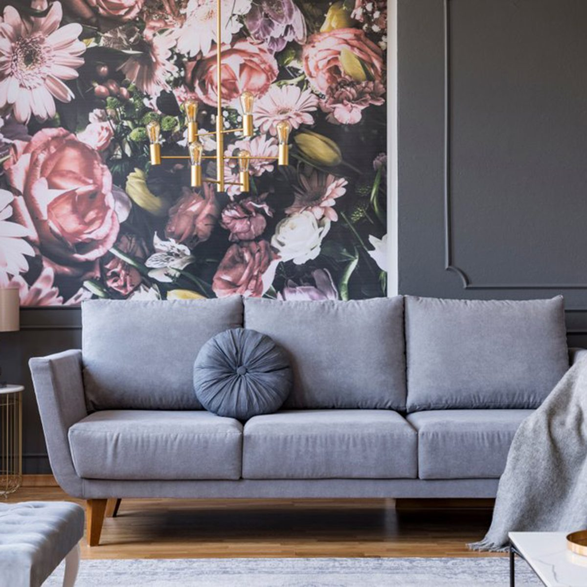 Grey sofa in front of a wall with floral wallpaper