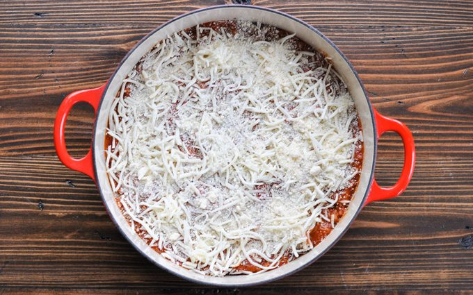 Layering lasagna ingredients in dutch oven