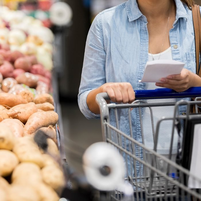 Person in a grocery store pushing a cart while reading their list