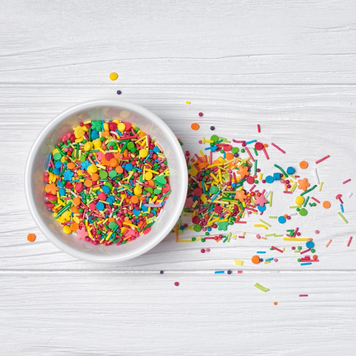 Top view of bright colorful sugar sprinkles or confetti in white bowl as baking decor