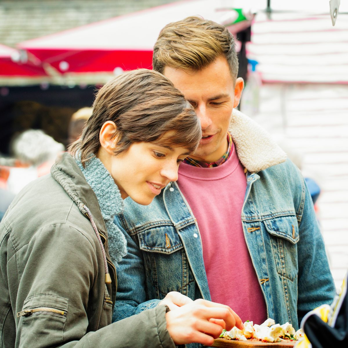 Young British couple sampling food at London market. They are dressed in Autumn clothing and the female is pickeing up chicken pieces to taste.