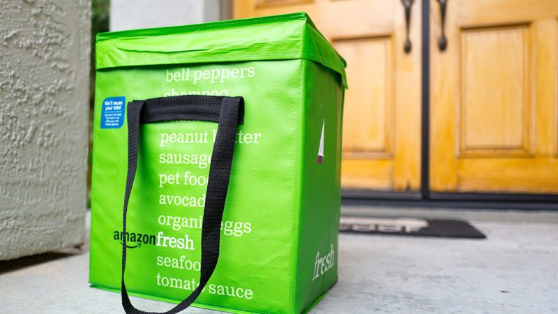 Green cold pack tote for Amazon Fresh grocery delivery service, with Amazon logo and text listing groceries which may be ordered using the service, on the doorstep of a suburban home in the San Francisco Bay Area town of San Ramon, California, April 11, 2017. In June of 2017, Amazon announced that it would acquire the upscale grocery chain Whole Foods Market to expand its offerings in the grocery industry. (Photo via Smith Collection/Gado/Getty Images).