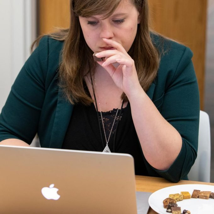 Woman eats small piece of protein bar while looking at laptop