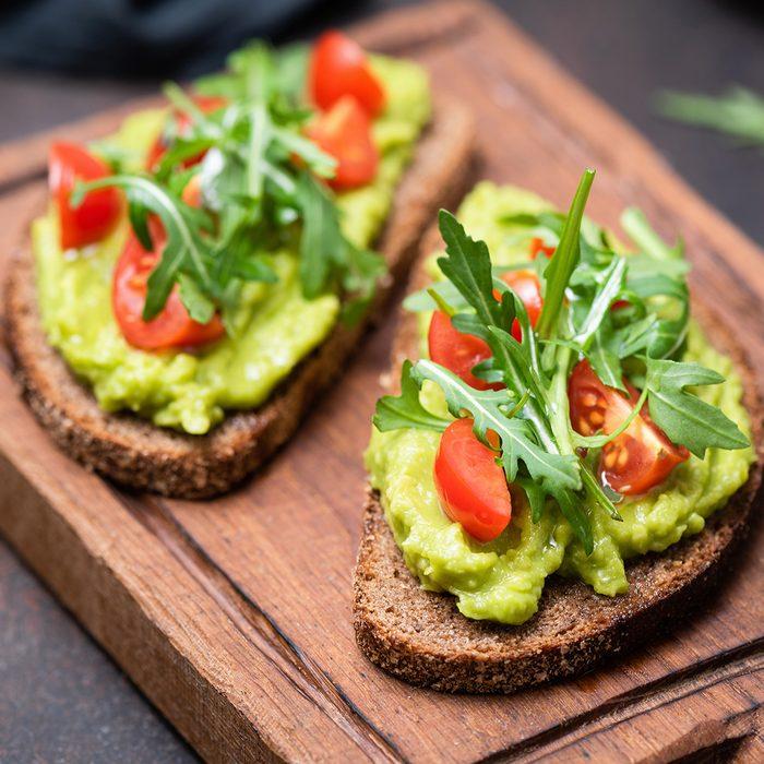 Healthy vegan toast with avocado, tomato, arugula on wooden serving board