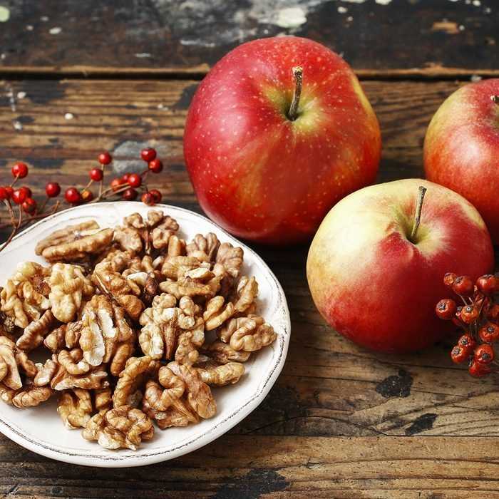 Bowl of walnuts and red apples on wooden table. Healthy snacks.