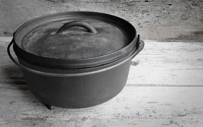 Cast Iron Dutch Oven With Old Wooden Background