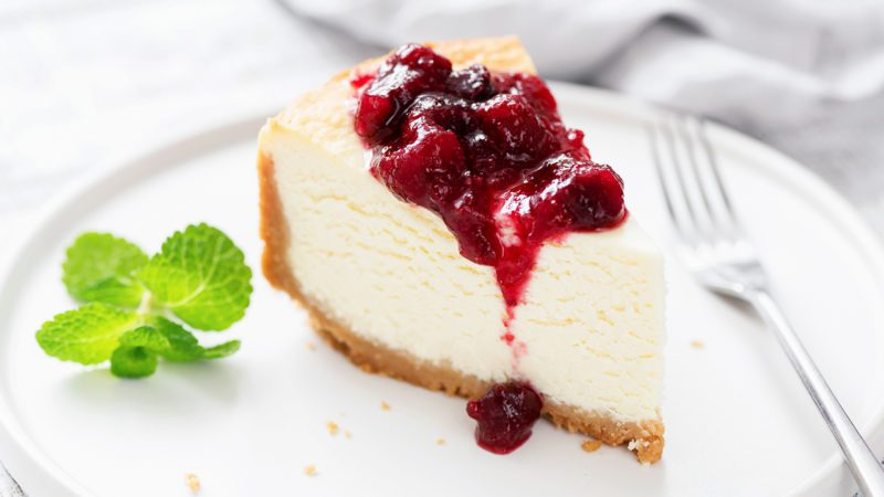 Classic Cheesecake With Cherry Sauce On White Plate.