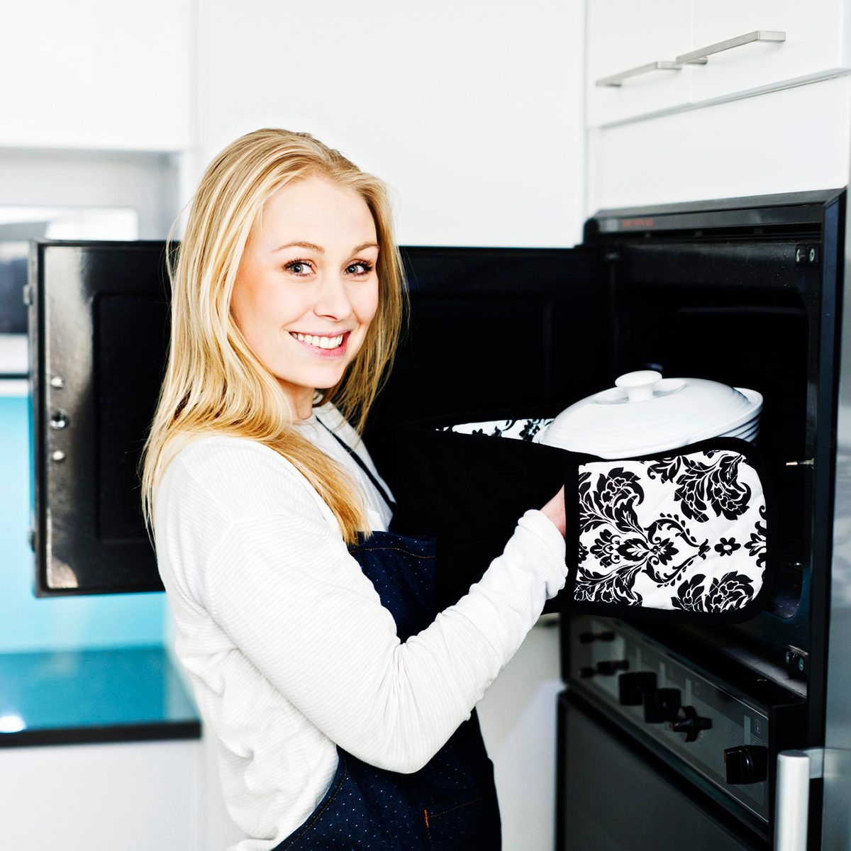 A beautiful young blonde woman looks up, smiling proudly, as she holds a casserole dish next to the oven in her modern, elegant kitchen. Here's to cooking success!