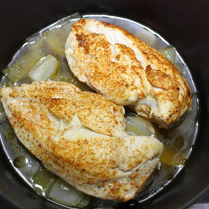 Delicious braised chicken breast cooked in a Dutch oven resting on the stove top in a home kitchen.