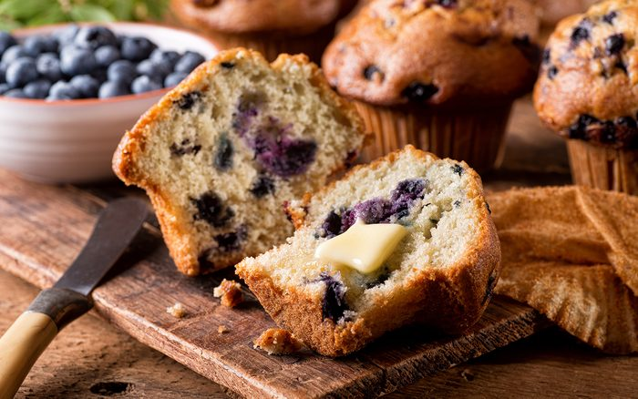 Fresh baked blueberry muffins with melted butter.