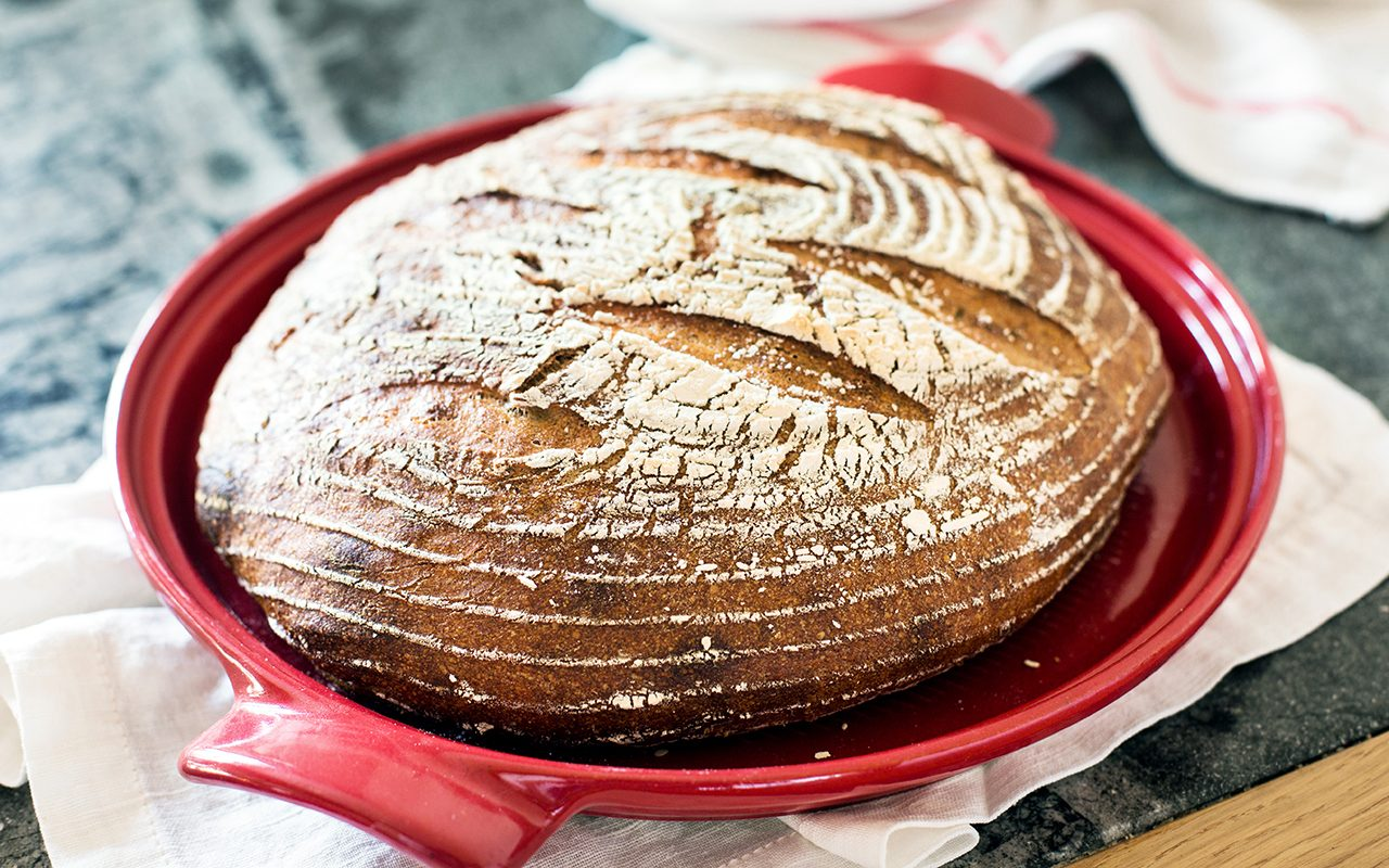 Freshly baked organic sourdough bread in a red dutch oven