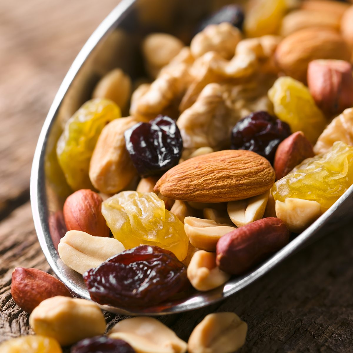Healthy trail mix snack made of nuts (walnut, almond, peanut) and dried fruits (raisin, sultana) on iron scoop