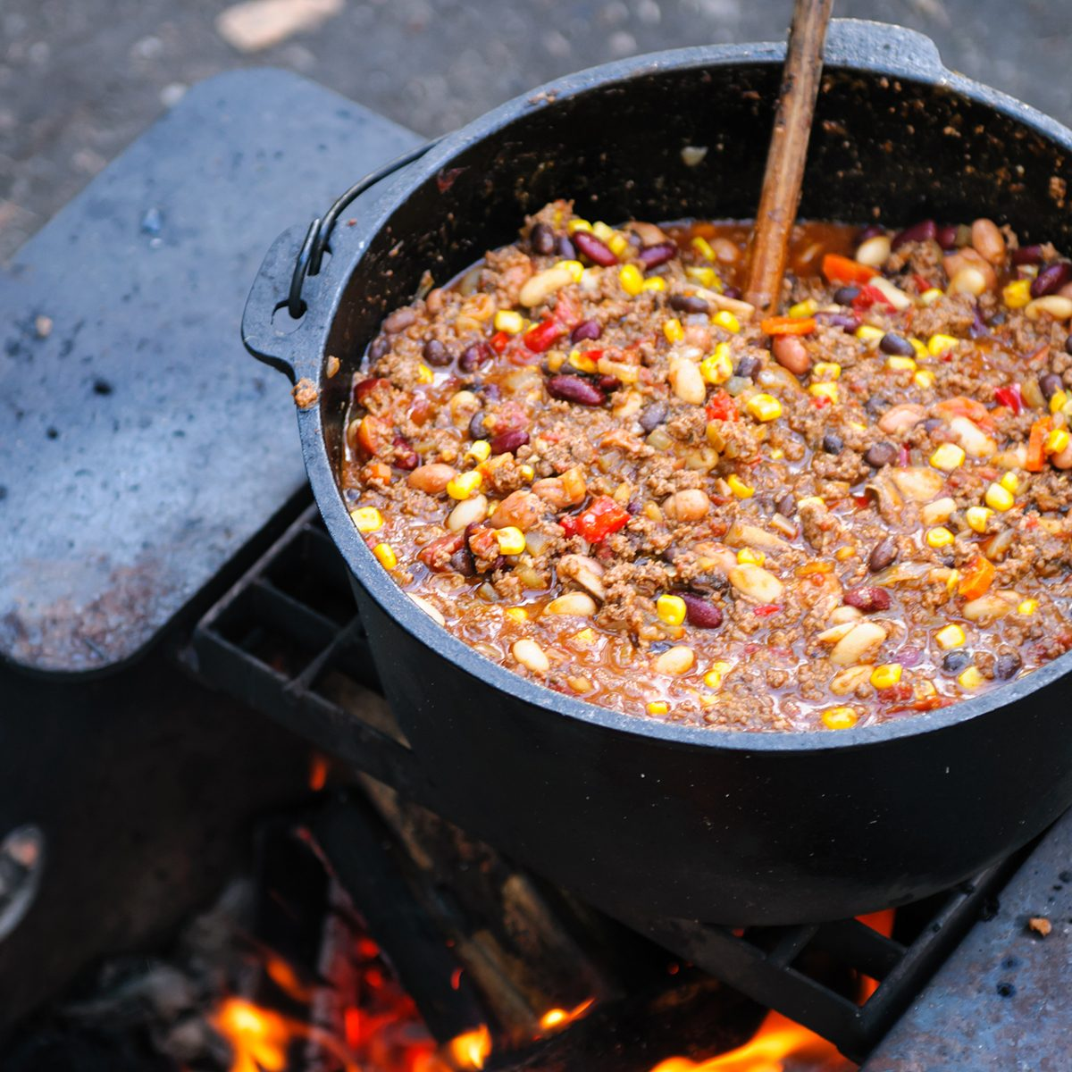 Large cast iron pot of spicy chili cooking over a campfire