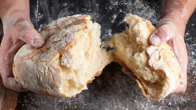 male hands breaking open baked bread in half over black wooden table
