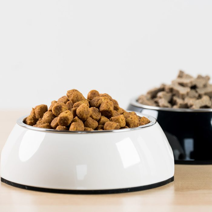 Two bowls of pet food next to each other, one white and the other black
