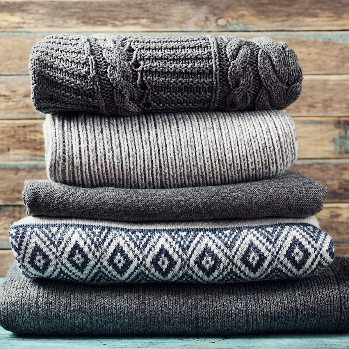 Pile of knitted winter clothes on wooden background, sweaters, knitwear