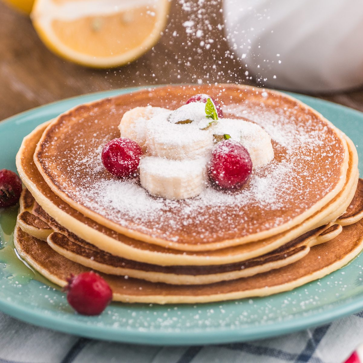 Pancake stack covered with honey, powdered sugar, banana and cranberries. On a wooden background in a blue plate