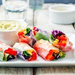 rainbow spring rolls with avocado white bean hummus on white wood background.