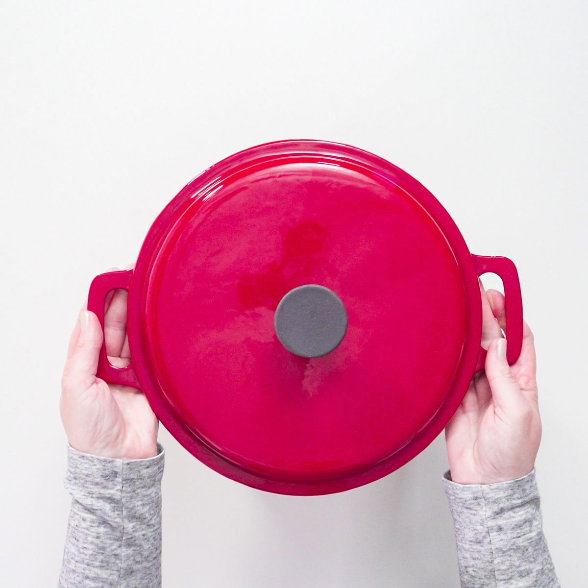 Flat lay. Red, white, and blue enameled cast iron covered dutch oven on a white background.