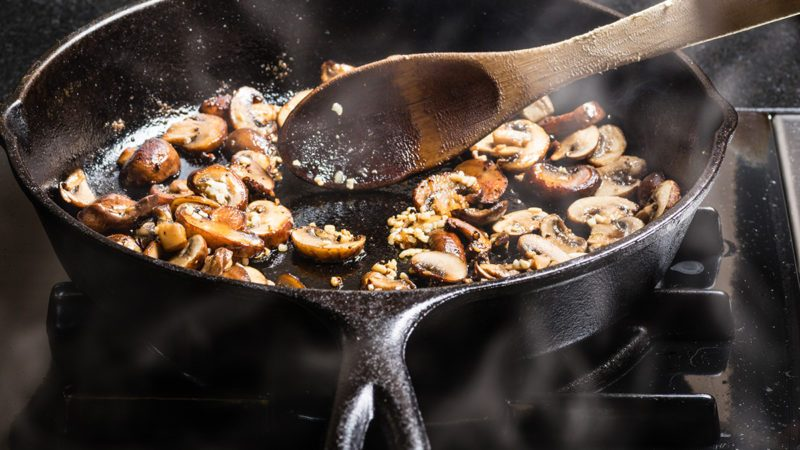 Sauteing sliced mushrooms in a cast iron skillet