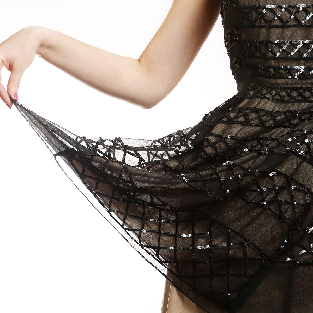 Sequin dress detail , Girl holding the hemline of her glamour sequin dress