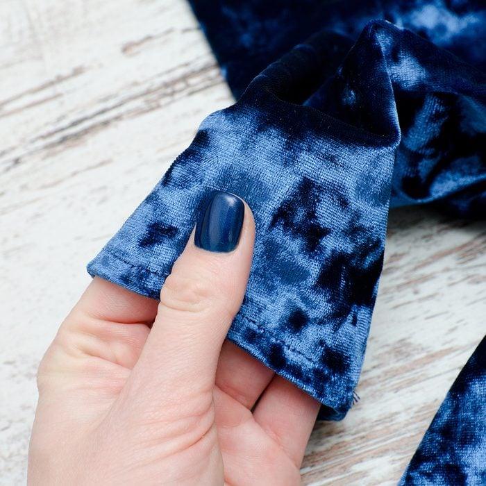 Sleeve of blue velvet dress in female hand. Fashionable concept