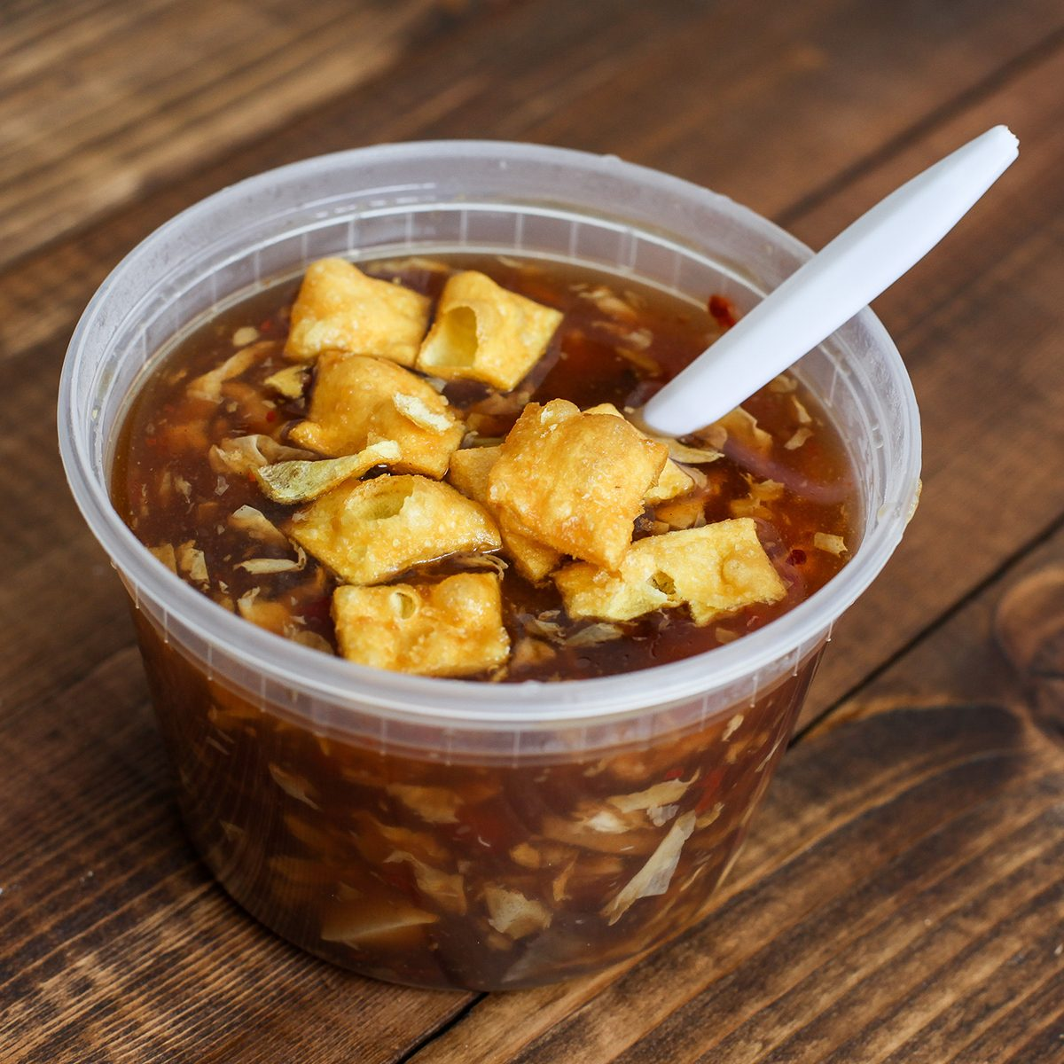 Hot and sour soup in plastic tray with spoon inside; Shutterstock ID 1582677055; Job (TFH, TOH, RD, BNB, CWM, CM): TOH