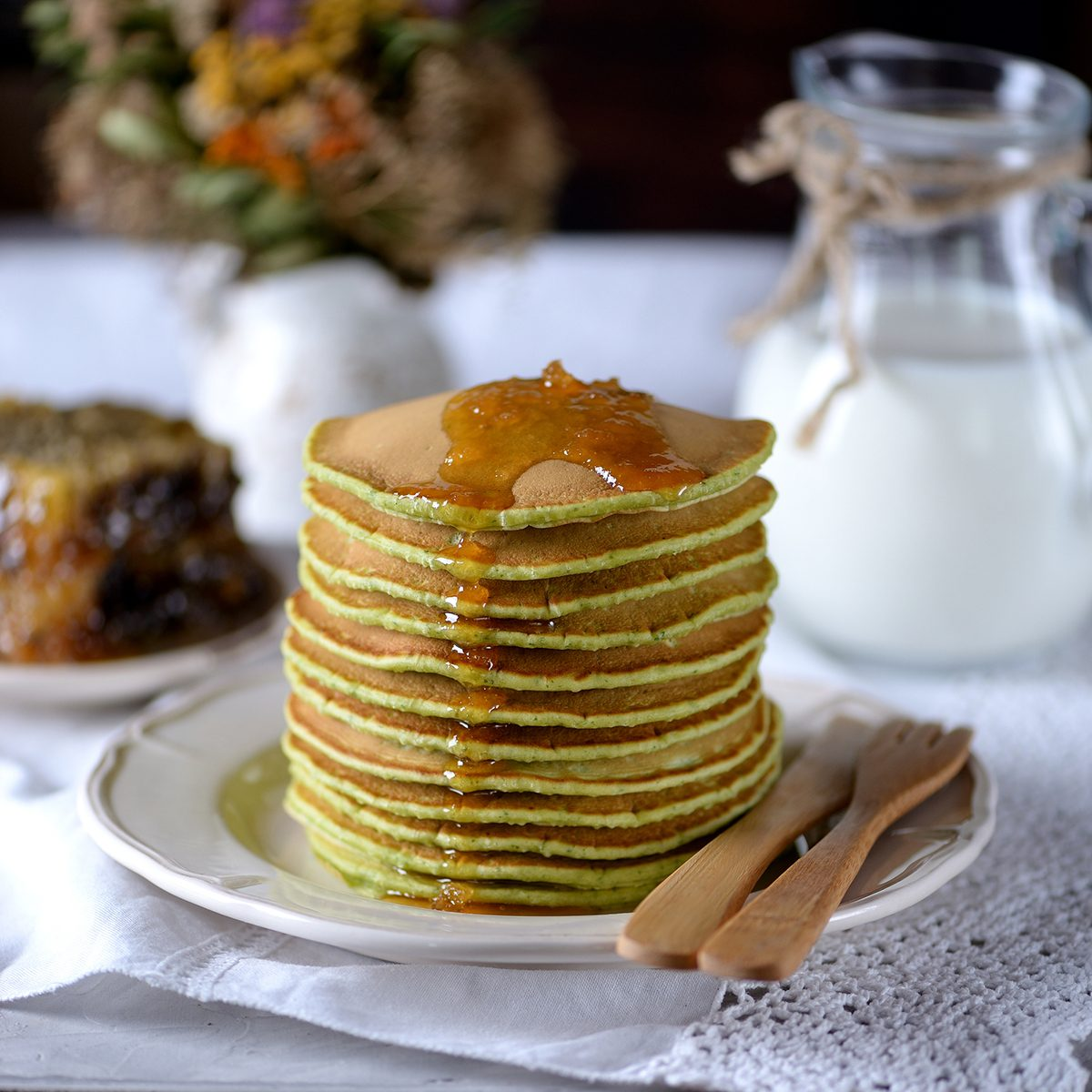 Spinach pancakes with milk and organic honey in honeycombs.