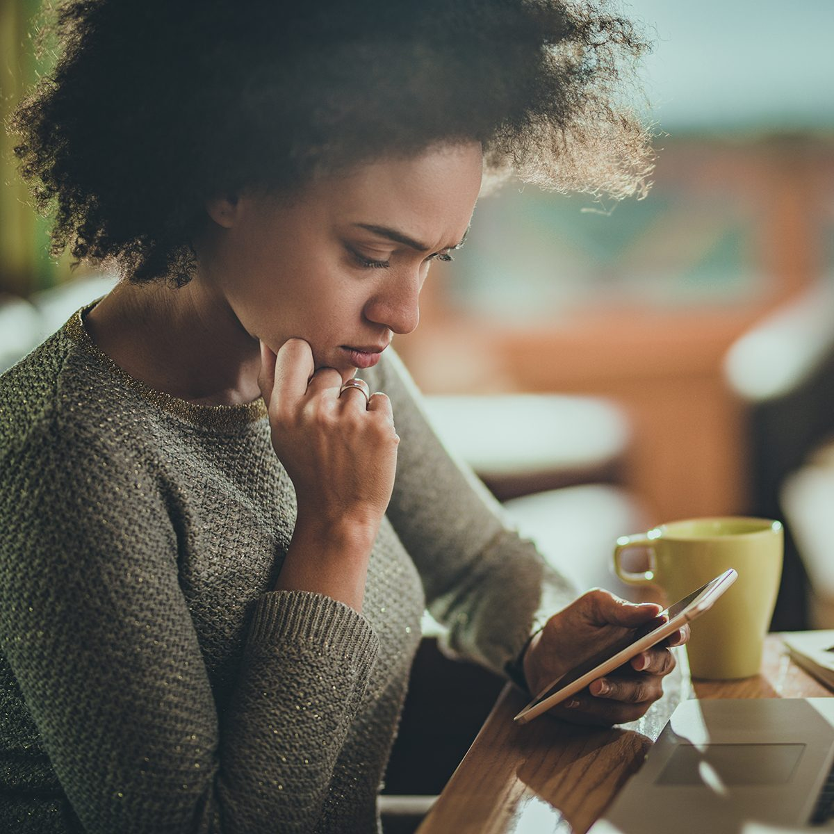 Young black woman reading a problematic text message on her mobile phone while working at home.