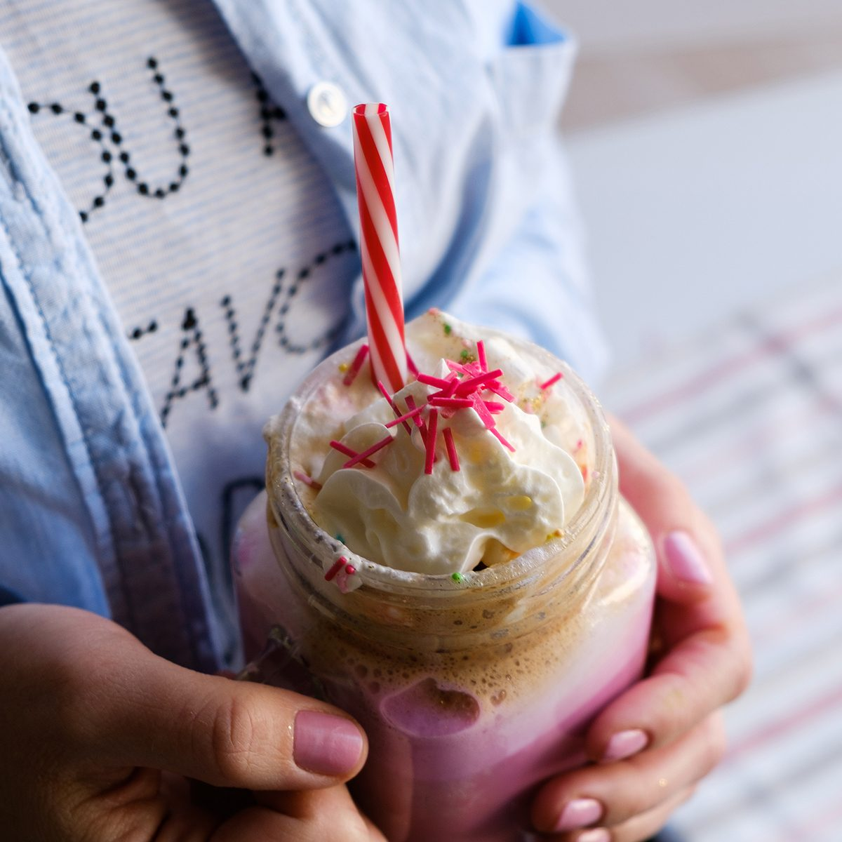 Girl is holding stylized mason jar cup of pink coffee with cream, marshmallow and decoration. Milk shake, cocktail. Unicorn coffee, unicorn food. Close up, soft focus