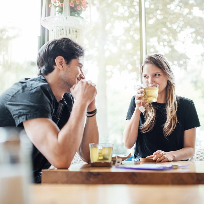 Young couple in love at cafe looking at each other and smiling. Woman drinking green tea and looking at her boyfriend.