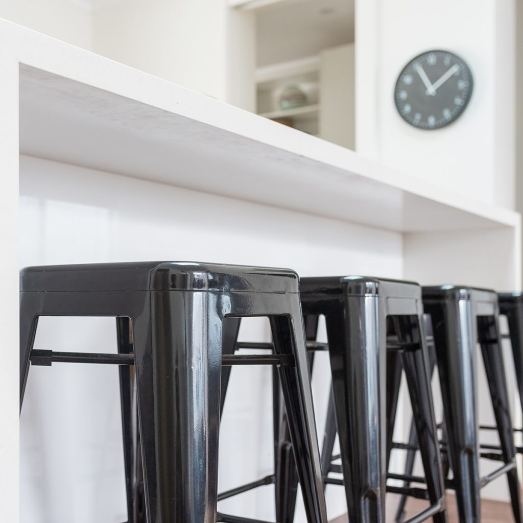 Closeup of black metal stools against white kitchen bench with clock in background (selective focus)