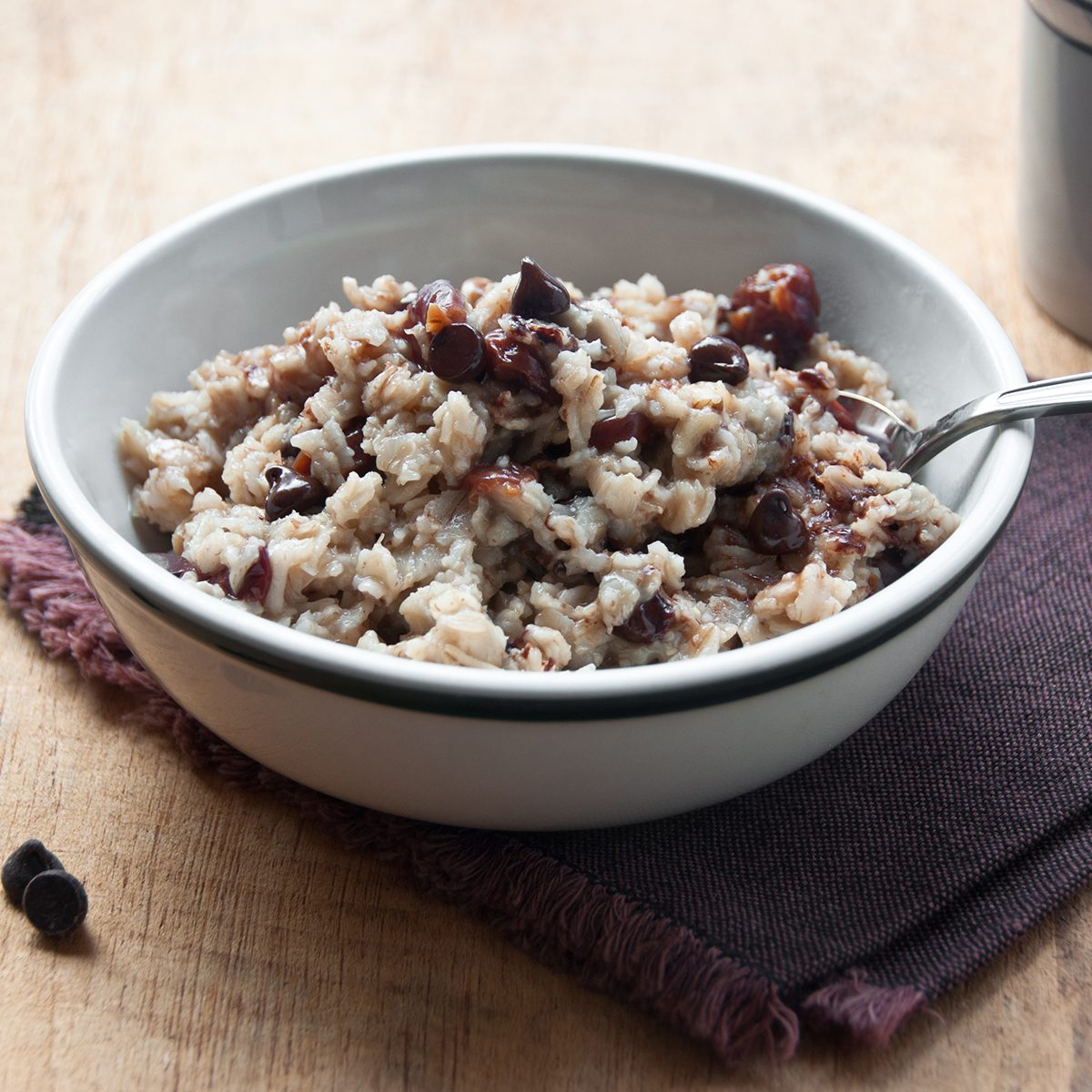 A bowl of oatmeal with dried sour cherries and chocolate chips awaits the morning diner.
