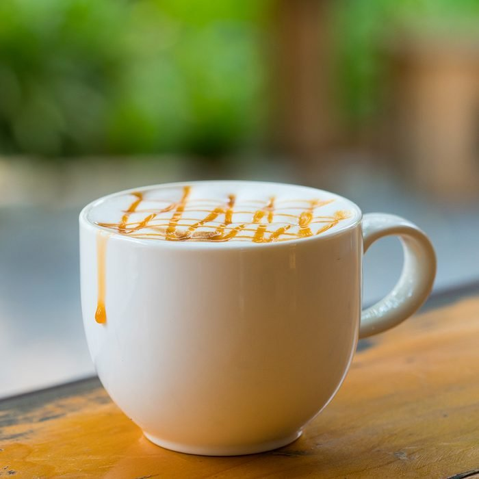 Hot Macchiato coffee with caramel in white cup on wood table by window light, copy-space background