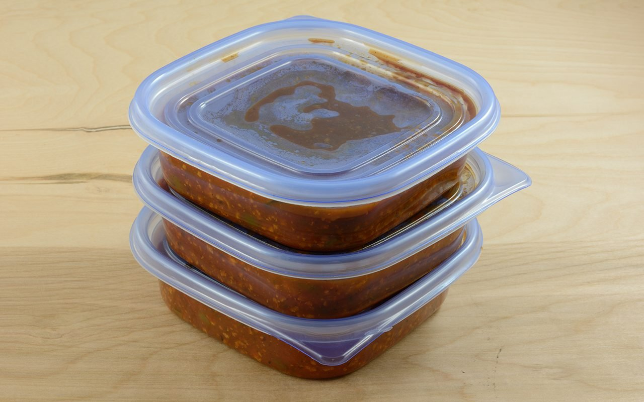 Batch of freshly made spaghetti sauce with ground turkey meat in plastic storage containers to prepare for freezer and meals in advance for work week