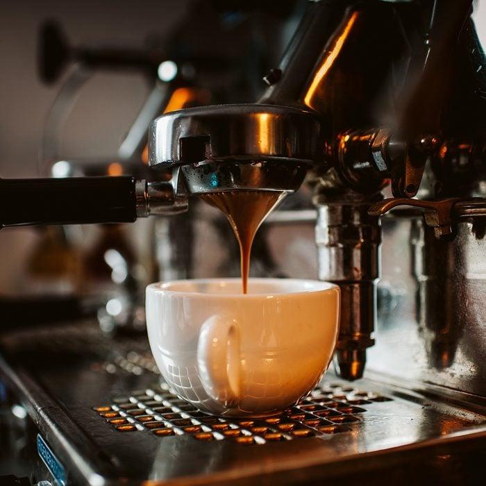 espresso machine pouring coffee into cups