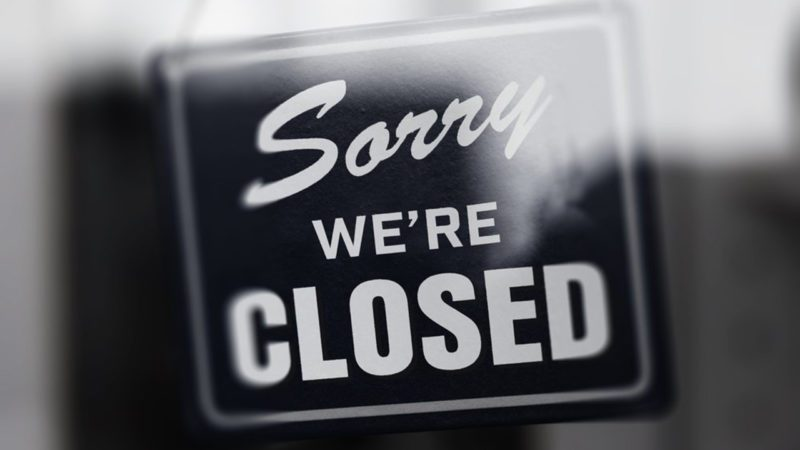 """"""" Sorry we're closed """" sign in monotone, with glass reflection. Shop glass door. Shallow depth of field."""