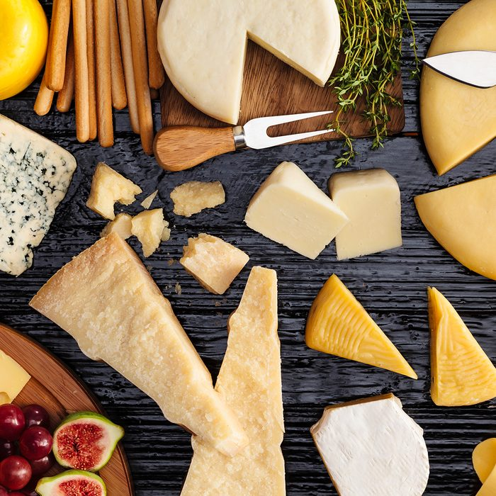 Top view of a dark table filled with a wide variety of cheeses.