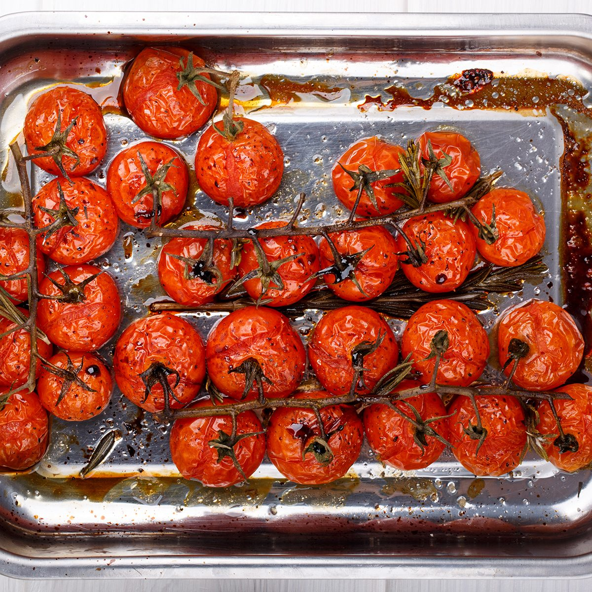 Cherry tomatoes on the vine roasted with herbs and balsamic vinegar. Top view.