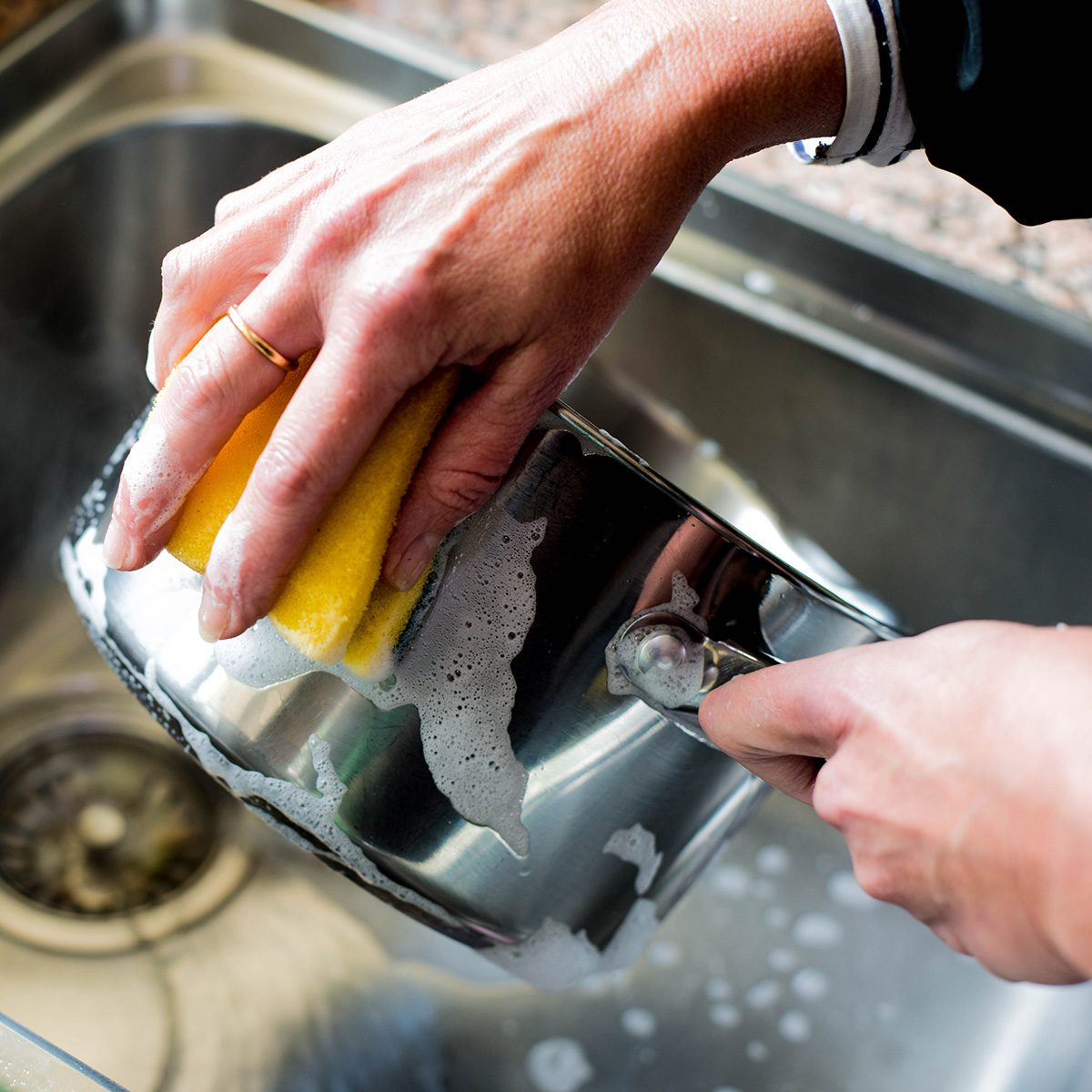 Woman Washing Up a Stainless Steel Saucepan in the Kitchen Sink After Cooking