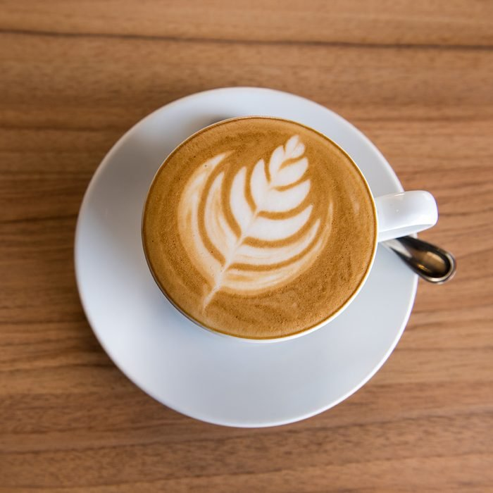 Flat white coffee on wooden table, Top view