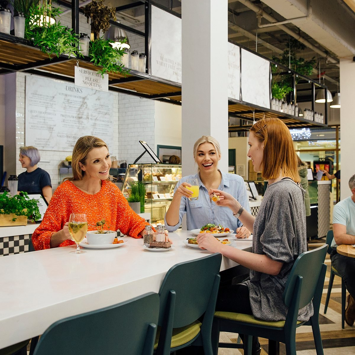 Three women are sitting at a table in a health cafe. They are eating organic, vegan meals while talking and laughing.
