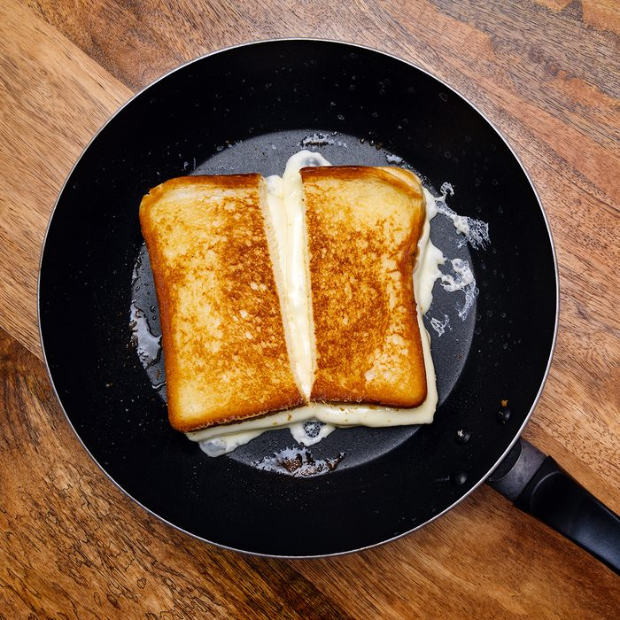 Photo of a grilled cheese sandwich cooking in a large frying pan.
