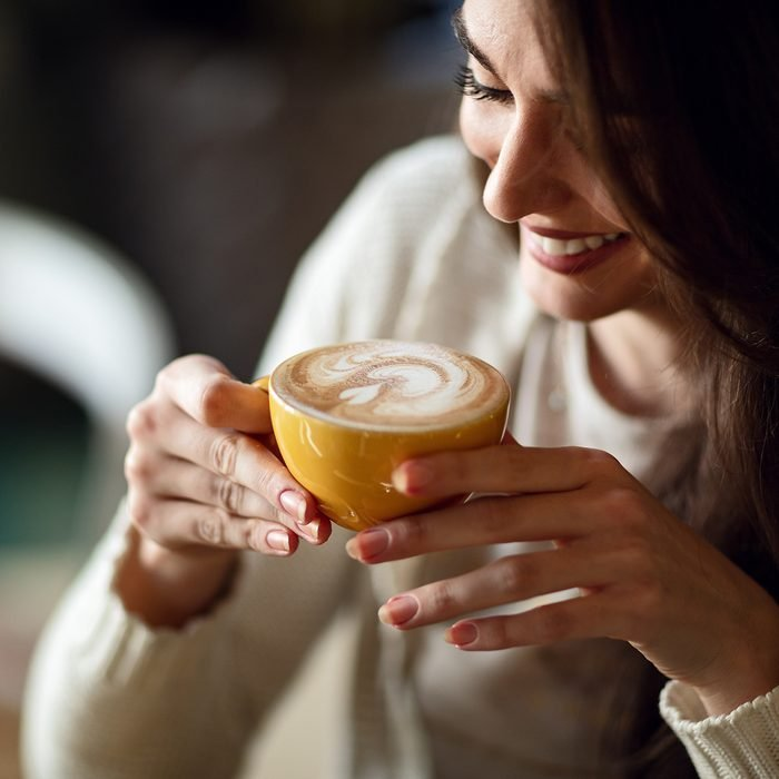 Young smiling woman holding cup of latte coffee.