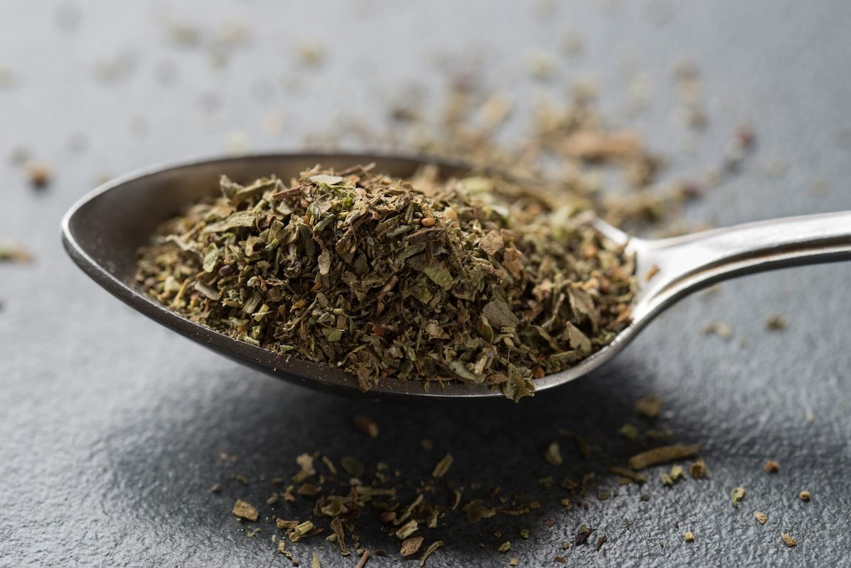 spoon of herbes de Provence on table macro