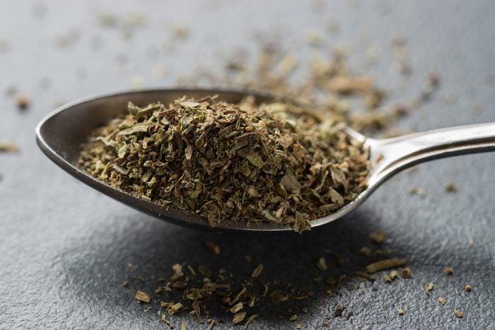 spoon of herbes de Provence on table macro
