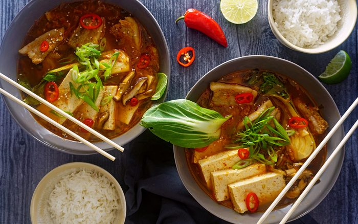 Two bowls of kimchi soup with sides of jasmine rice overhead zoomed out